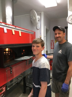Smiling, standing by the pizza oven